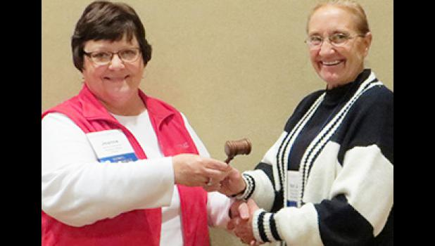 Past SDML President Jeanne Duchscher, left, passes the gavel to newly elected President Meri Jo Anderson after Anderson's election in Aberdeen.