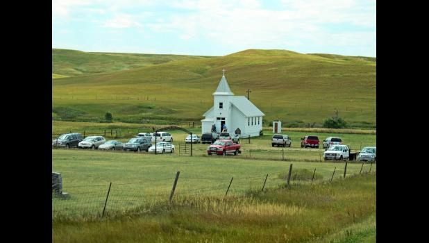A large number of cars parked around the church for the services on July 24.