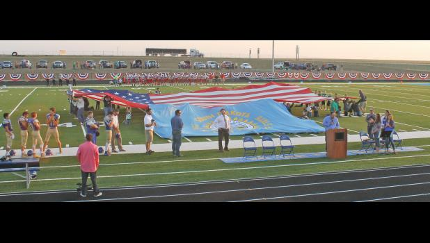The dedication of the Wall School District's outdoor athletic facility included volunteers holding up a huge American flag, as well as a slightly smaller South Dakota state flag.