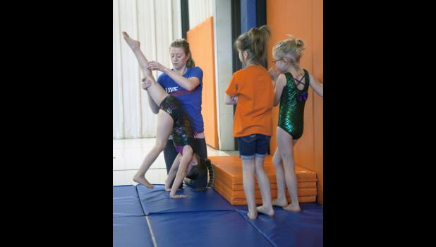 Abby provides step by step instruction to the young gymnasts.