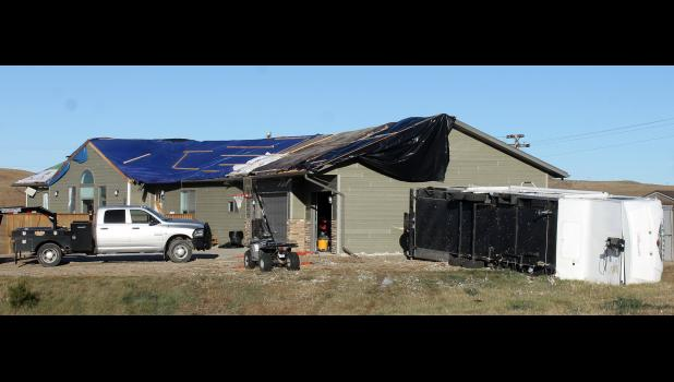 Grain bins to the west, houses to the east, and football field lights to the south were not damaged, yet the Fitzgerald house took the brunt of the wind storm late Monday afternoon. The house and garage roof were gone. A camper was tossed onto its side. Within minutes well over 30 people were helping patch up the roof and move furniture inside the house.
