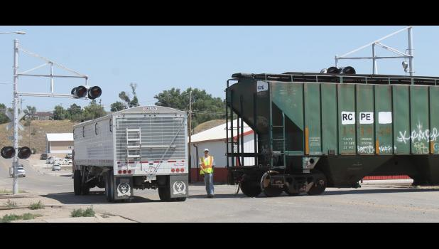 A truck is directed around a railroad car. The truck just emptied its load of winter wheat, and the train is being loaded. A quick figuring is: 37 train cars equal 120 semi-trucks, which equal about 120,000 bushels of wheat.