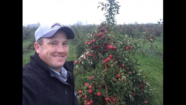 Josh Geigle toured an apple orchard. The trees can be worked from ground level. The only machine is the scoop that collects the not-quite good enough apples that are purposefully dropped to the ground to eventually become juice, sauce and other by-products.