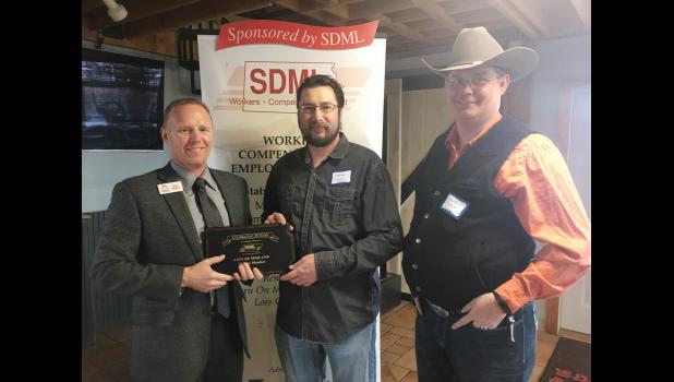 Town Board Vice President Derek Flom, center, and Board Trustee Dakota Fosheim, right, accept a plaque from Brad Wilson, South Dakota Municipal League workers' compensation fund administrator.