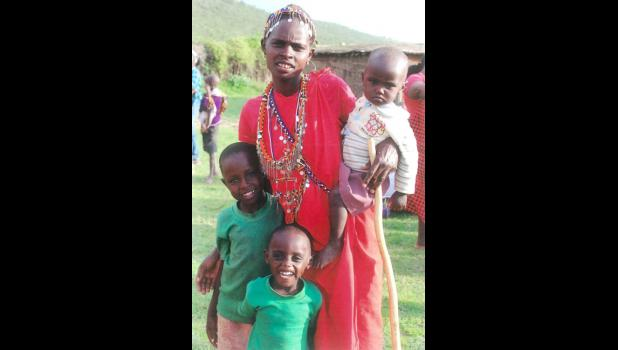 A young Maasai woman poses with her three children. Her husband would be considered well on his way to wealth, since wealth for the Maasai is measured in cattle and children.