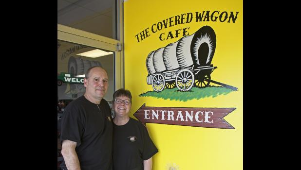 Owners of the Covered Wagon Cafe Russ and Missy Wilbur pose in front of the freshly painted cafe entrance.
