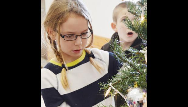 Malayne Condra, third grade, carefully places her ornament as her classmate, Tyler Cook, takes in the wonder of the class tree.