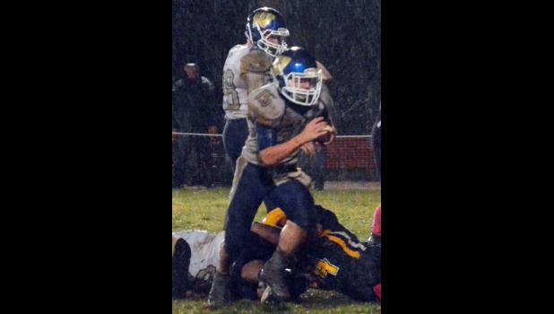Wall Eagle Carter Elshere (#15) with the football and Camden Sawvell (#28) in the back ground at the rainy Oct. 22 football game in New Underwood.